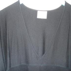 Varetype: Kjole i skøn afslappet stil med 30% uld Farve: Sort  Skøn og afslappet kjole i sort 30% uld og 70% Viskose i størrelse Large fra Benedikte Utzon. V-halsudskæring, velplacerede sømme, lommer i sidesøm, smart lynlåsdetalje i de 3/4 lange ærmer. Måler over brystet 122 cm, og længden er 94 cm. Brugt få gange og fremstår i flot stand. BYTTER IKKE!