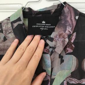 Silkeskjorte i grafisk print med skjulte knapper. Kan bruges både i hverdagen på arbejdet og om aftenen med et glas rødvin.