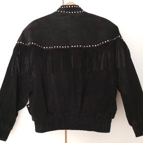 Vintage leather jacket with fringes and studs along the chest and back.
