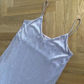 Stropkjole fra H&M i sølv plisse. Super flot og kun brugt en gang til bryllup. Kjolen kan styles med en t-shirt under eller bruges alene. Slids i den ene side. Let stræk. Blød i materialet.