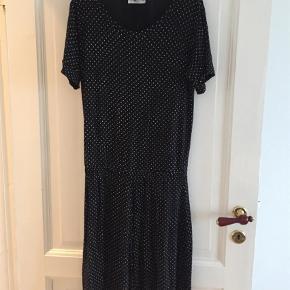 Varetype: Midi Farve: Sort Oprindelig købspris: 600 kr.  Sort kjole med små hvide prikker og elastik i taljen. Blød kvalitet.   Brugt få gange.