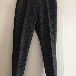 Brugt 2 gange købt for små  Mørke grå bukser med zebra mønster og panel i sidesømmen samt pressefold.  Ny pris: 1299kr  Kan sendes på købers regning