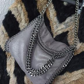 Fin kædetaske i grå  Har en lynlås lomme samt to små lommer til fx telefon indeni  Ca 26 bred. 25 høj åben og 20 lukket  Mp 200