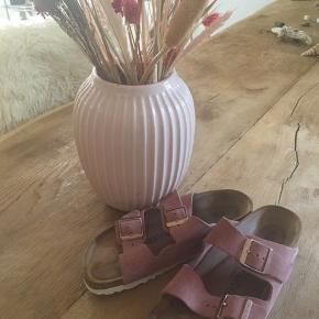 Klassisk Birkenstock sandal i lækkert  rosafarvet ruskind. Kan justeres med 2 spænder. Sidder utrolig godt på foden og er meget behagelig at gå i pga. Birkenstocks unikke fleksible korksål. Bemærk den cremefarvede/lyse sål under sandalen.