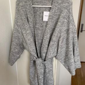 Grå oversize cardigan sweater med bindebånd og lommer i str. one size fra Moss Cph. Sælges for under  halv pris plus porto Længde ca 85 cm Bredde ca 60 cm fra ærmegab til ærmegab Ærmer (3/4) målt fra armhule pga lav skulder søm ca 33 cm. Materiale mix - se billede! Model: LU