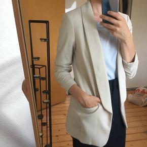 Beige H&M blazer med ruffle-sleeves. Brugt få gange. XS men passer også en S.