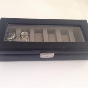 Flot og stilren aflang urkasse ⌚️ m/display til 6 urer. Beskytter dine urer mod ridser, smuds og støv. En form mangler.  Materiale: slidstærk sort PU læder.  Nypris: kr. 299,-