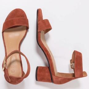 Helt nye sandaler i ruskind og med en blokhæl på ca 5,5 cm i højden.  Lidt store i størrelsen.   Aldrig brugt. Skoæske medfølger.