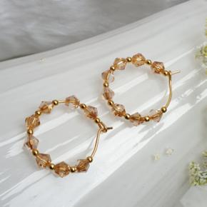 Hjemmelavede øreringe med små koniske krystaller, på nikkelfri guldtone hoops, diameter 2,1 cm.  Æske kan tilkøbes for 5 kr.