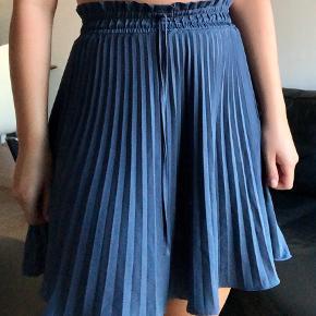 Fin plisseret mini-nederdel 💙💙 falder flot, og med elastik bånd i taljen, samt lille bindebånd.
