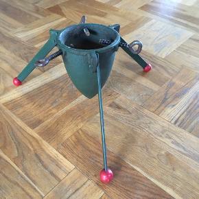"""Juletræsfod fra 50'erne / 60'erne. Støbejern med grøn bemaling. 3 ben med røde """"træknopper"""". Lidt rust og brugsspor. Benene kan slås sammen, så den ikke fylder så meget under opbevaring."""