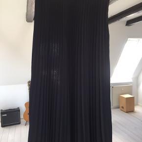Plisseret nederdel i 100 % polyester.