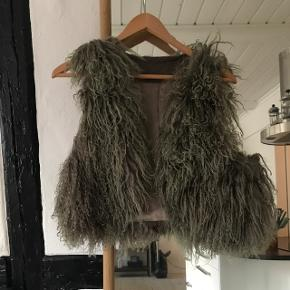 Grå/beige lammeskinds vest. Den har nogle misfarvninger i pelsen (er dog stadig fin) og sælges derfor billigt. Sælges kun, da den ikke længere er mig.