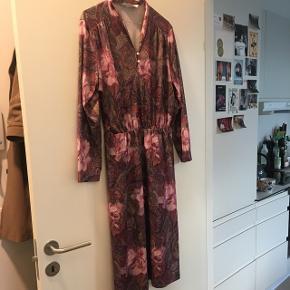 Smuk vintage kjole med fine detaljer, elastik i taljen og lille V-udskæring ved halsen. Falder smukt og sommerligt ned langs kroppen. Str. passer til alt fra en str. S - M - L, alt efter hvordan man ønsker at bære den :)