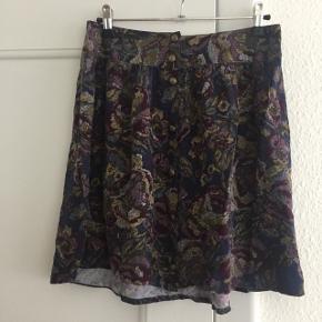 A-formet nederdel fra Pins and Needles (købt i urban outfitters). Blomsterprint i afdæmpede lilla farver. Lukkes med knapper hele vejen ned foran. Sender gerne med DAO :)