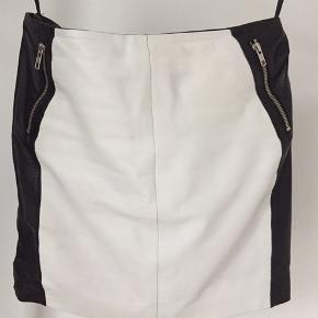Lækker lammeskinds nederdel , i sort/ hvid skind, ikke brugt mange gange, da den er for stor til mig, nypris 1499kr længde 41 cm
