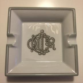 Porcelæn askebæger/skål fra Christian Dior  Christian Dior vintage porcelæn askebæger (kan bruges som et lille fad/skål til smykke) fra Christian Dior med monogram.  Størrelse 10 x10 cm. I fin stand uden ridser.