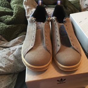 """Adidas Stan Smith 80's """"Suede Pack"""".  Lækker Adidas sko fra 2011. Står i rigtig god stand. Flere billeder kan sendes via mail. Boks medfølger ikke, men snørebånd gør.   Jeg er samler, så passer godt på mine sko. Nye som gamle. Alle sko vil blive rengjort og renset i hånden inden salg.   Jeg er i gang med at sælge en stor del af min samling, grundet operation (og pladsmangel).   Prisen her er 399,- for en sko der ikke er til at opdrive, så skal du have en sko du ikke ser alle andre gå i, så smid en besked. Priser kan forhandles.   Forsendelse betales af køber, eller der er mulighed for at mødes i Århus C.   Kig eventuelt mine andre annoncer for flere sko."""