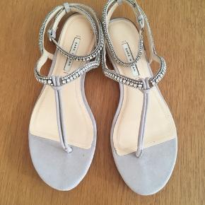 Super smukke og elegante  lysegrå sandaler str. 37 sælges. De er købt til min datter, men da hun aldrig har fået dem brugt, har jeg beslutter mig for at sælge den. Se også mine andre spændende annoncer., da jeg bl.a. sælger ud af klædeskabet. Jeg sender gerne ved betaling med MobilePay. Porto GLS 35kr.☀️🌸☀️