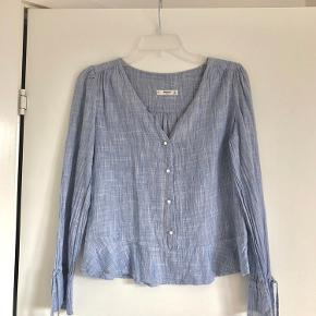 Beautiful Mango blouse in white/blue stripes and pearl buttons. A little shorter in length, so looks great with high waisted jeans under. The sleeves can be tied. Super soft and lightweight material, but easy to wear something underneath for the colder months.