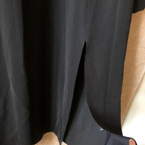 1990: Flot, lang sort kjole fra & Other Stories med slids og lange ærmer.  Ru kanter. Lynlås ved håndled. A-form.  Havde oprindeligt to slidser, men jeg har syet den ene til (kan nemt åbnes igen).  Skulder: 84cm Bryst: 92cm Talje: 88cm Længde: 120cm Ærmer: 64cm  Polyester.