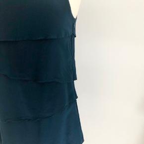 Flot kjole i lag-på-lag i petrol fra Philosophy Blues uden ærmer. Lukkes med lynlås på ryggen og skjult lynlås i venstre side. Der er en dejlig blød underkjole. Længde fra skulder er 91 cm, brystmålet er 90 cm, og taljen måler 88 cm. Fremstillet i lækker, blød silke. Bærer ikke præg af brug.