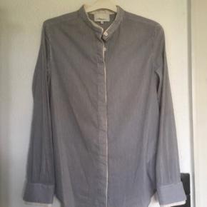 Super lækker skjorte bluse fra Phillip Lim. Skjult lukning ned foran.  Blødeste bomuld / silke.  Har fine smalle sarte lyseblå og hvide striber. Fremstår som grå / gråblå.  Angivet som str 2 - svarende til str S Str 36 - lille 38