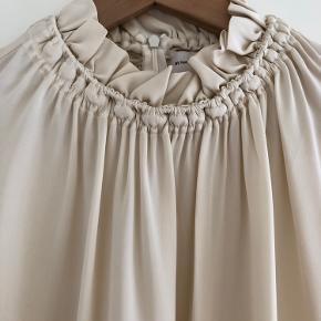 Aldrig brugt, prisskilt er dog klippet af.   Lækker silke kvalitet med lidt stretch.   Er fra SS2020 kollektionen og er også super smuk under en cardigan til efteråret.   Prisen er fast.