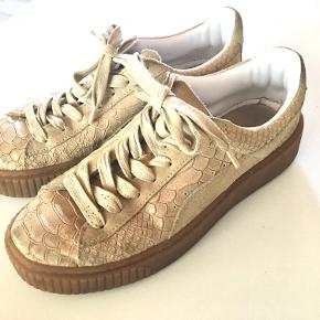 Sandfarvede puma sko med tekstur. De har en lille smule glimmer i stoffet.