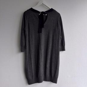 Skøn kjole i 100% blød uld fra COS. Så fin detalje med en mørkeblå sløjfe i ryggen. Kjolen har en mikroskopisk reparation efter et hul, men det er ikke noget, der kan ses når den er på.   Søgeord: H&M, COS, Wood Wood, Samsøe Samsøe, Ganni, Filippa K, Zara, Envii, Nike, New Balance, Adidas