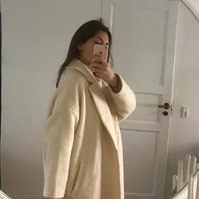 Råhvid halvlang uldfrakke fra H&M. Er en str. M, men svarer til L, da den er oversize. Designet til at stå åben (uden knapper).  Med lommer. Jeg er en str. S.