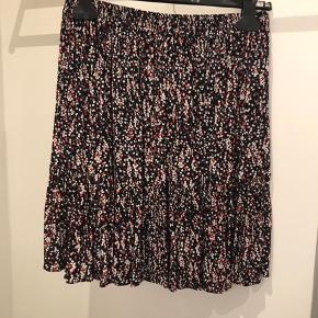 Fineste nederdel med røde/ hvide blomster og elastik i taljen.