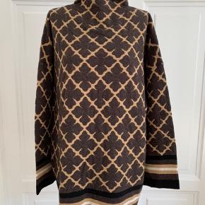 Næsten som en poncho - og så alligevel ikke… Denne oversize-sweater med høj hals er bare et musthave til din vintergarderobe. Den er forsynet med vores karakteristiske Signature Flower motiv og et halstørklæde-lignende kontrastbånd ved sømmen, så den både er elegant og enkel på samme tid. 80% uld - merino, 20% polyamid Size : L