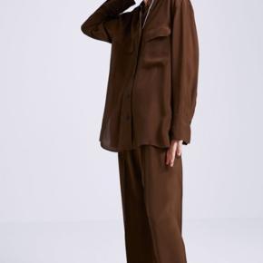 Brune bukser med brede ben. Løstsiddende, højtaljede bukser med elastisk linning, lommer foran og markante syninger foran.  Str. M. Aldrig brugt. Mærke sidder stadig på. Nypris 549kr.