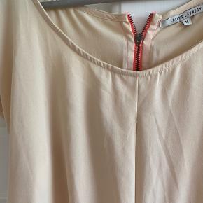 Top med kontrastlynlås i ryggen. Rummelig model. Længde 67 cm. Brystvidde 53*2 cm.