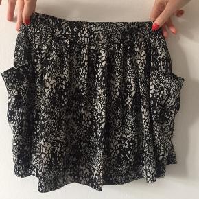 Plastic Island (US brand) nederdel. Sort/hvid mønster. Brugt to gange. Elastik i livet.   Længe: ca 41 cm foran og ca 42 cm bagtil.  Materiale: 100% polyester