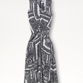 Hop i denne romantiske kjole, og mærk straks, hvordan den bløde silkeblanding og den perfekte draperede pasform forvandler dit look. En simpel underkjole-silhuet tilført volumen og form takket være rynkerne foran, der smyger sig ud i sidelommer og en sænket talje. De vintageinspirerede blonder gør den mere unik, mens farverne gør den moderne.  Kjolen er brugt en gang, og har i den forbindelse desværre fået en lille plet nederst.  BEMÆRK: jeg sælger også skjorten, som modellen har inden under kjolen!   Materiale: 66% viskose, 34% silke. Mål str. 34: bryst 41,5cm, talje 35,5cm, hofte 49,5cm, længde 133cm.