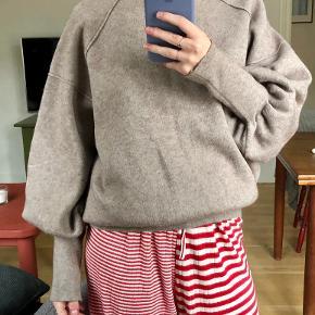 Lækker oversize sweater med fine puffede ærmer og høj hals. Standen er som ny.