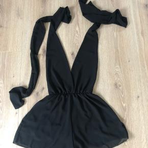 Sort buksedragt / playsuit/ jumpsuit ligner lidt en kjole str onesize, vil sige den passer xs til m.  Købt på en ferie i sommers, brugt en gang  Man kan lukke den som man ønsker. Nypris 600