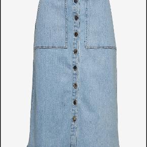 STELLA NOVA – WENYA NEDERDEL  A-formet denimnederdel med knapper hele vejen ned foran. Nederdelen har lommer foran og bagpå. Nederdelen er produceret af 100% solenergi. 92,5% Cotton, 5% Polyester, 2,5% Elastane