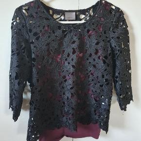 Fin sort bluse med blomster som kan bruges over en farvede top.