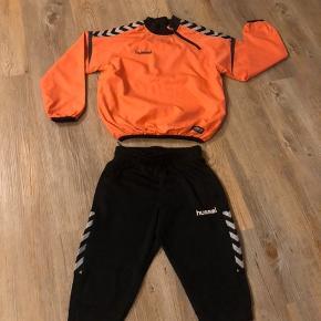 Super lækkert fodboldtøj str. 140. Kun brugt få gange. Der er en orange windbreaker og et par sorte fodboldknickers.