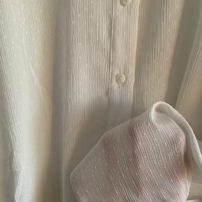 Skjortebluse i tyndt og let materiale. Den er en smule gennemsigtig og har fine flæsedetaljer. Fejler intet!