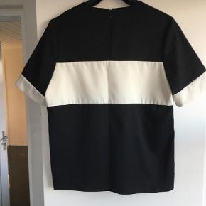 Varetype: Bluse Farve: sort / creme  Fin og lækker bluse i sort med creme farvet stribe på brystet og på ærmet og med lille lynlås i nakken.  Velholdt - rigtig fin.  Skal blusen sendes indenfor DK aftales portoen med sælger.  Materiale er  54% polyester - 44% wool - 2% elastane   Mål er Længden 64 cm Brystmål 2 x 49,5 cm    *** BYTTER IKKE ***