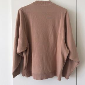 Orange/laksefarvet sweatshirt fra Monki. Den er str. XS, men er meget oversized.