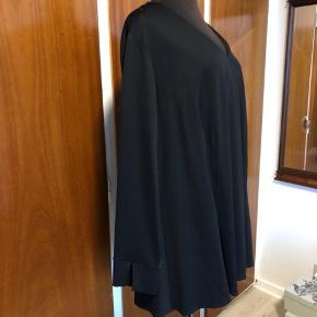 Elegant sort bluse fra Que med lange ærmer og lynlås i nakken. Falder enormt flot.  Str.56. Helt ny og ubrugt. 73%viskose, 24% polyamid, 3% elastan  Mål: Bryst 71cmx2 Talje 70cmx2 Kan give sig! Længde 80cm Sender gerne:) Til salg flere steder