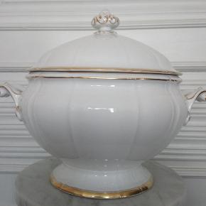"Brand: Bing & Grøndahl Varetype: Offenbach Suppeterrin Størrelse: H. 27 cm Dia 33 cm/ inkl. hanke Farve: hvid og guld  Bing & Grøndahl - Offenbach suppeterrin (323). 1. sort, men har en lille glasurrevne på den ene hank. Monogram EW på den ene side.  Elegant tidløst hvidt porcelæn med dekoration i guld - oprindeligt markedsført som ""Kronprinsestellet"", da det blev foræret i bryllupsgave til det daværende kronprinsepar - senere Christian den 10. og dronning Alexandrine."