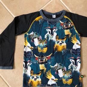 """Super lækker bluse fra skønne Molo, str. 140. Blusen har print med flotte farverige fantasidyr, foran og bagpå, og mørke ærmer.  Standen er sat som """"næsten som ny"""", da den er vasket på 30 grader en enkelt gang, men jeg mener ikke den har været brugt overhovedet. Den er sååååå fin ☺️   Se også mine andre annoncer. Se om der er mere der frister 😊 Jeg har rigtig meget drengetøj i den størrelse 👍🏻🙈"""