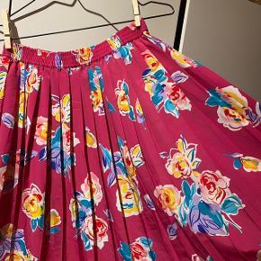 Smuk plisseret vintage nederdel med blomsterprint på pink baggrund.💐 Svarer til en str. 36.  Kan afhentes på Amagerbro eller sendes med DAO (køber betaler Porto). Byd gerne, mængderabat gives.