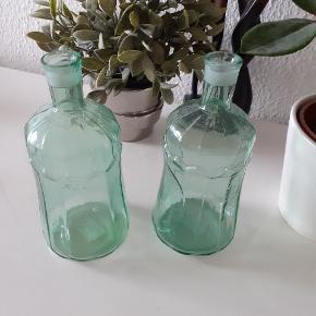 2 stk grønne glasflasker. højde:  19 cm dia: 8 cm  (målt i bunden)  Flotte med stearinlys i, eller andet pynt. Nye og aldrig brugt.